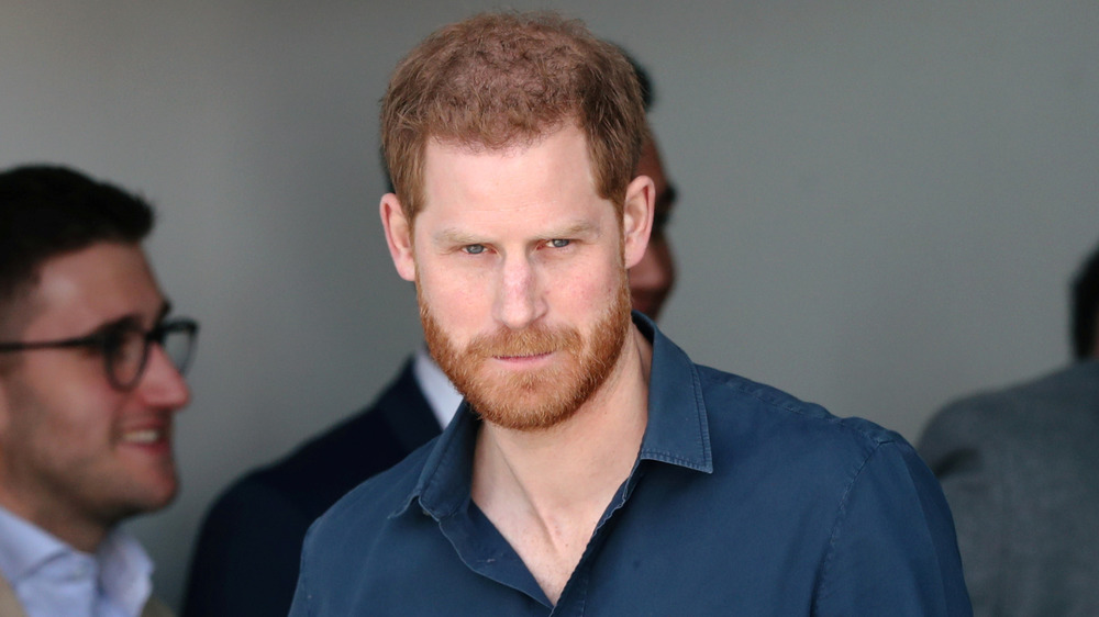 Prince Harry looking serious in the crowd