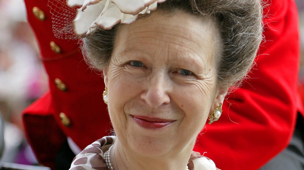 Princess Anne poses in a white hat.