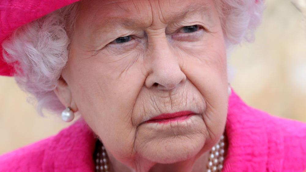 Queen Elizabeth II looking serious in hot pink
