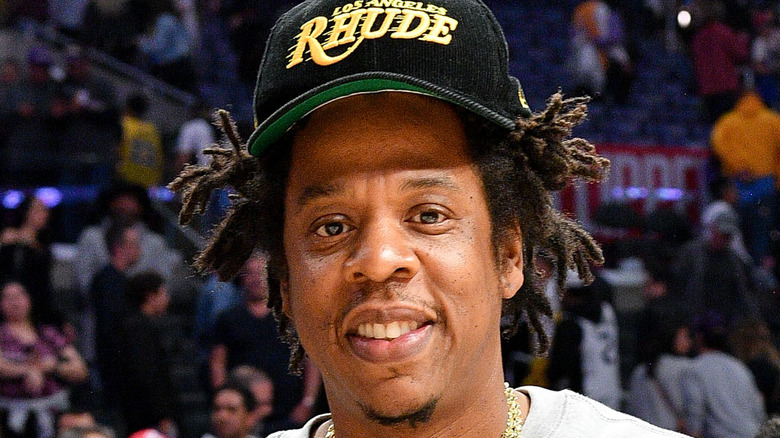 Jay-Z wearing a black cap and smiling