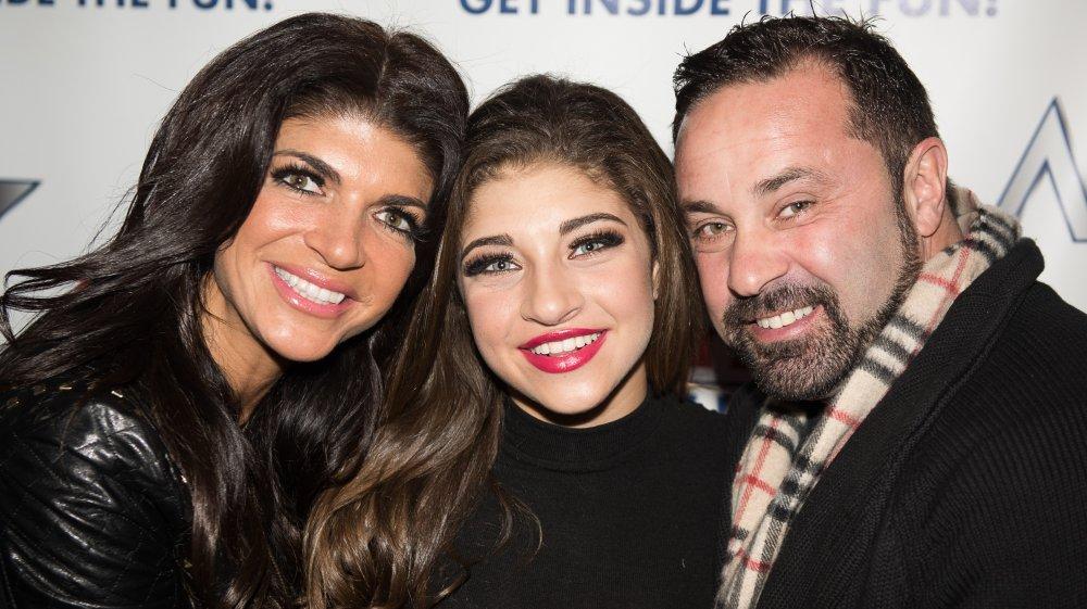 Teresa Giudice, Gia Giudice, and Joe Giudice smiling and embracing at a red carpet event