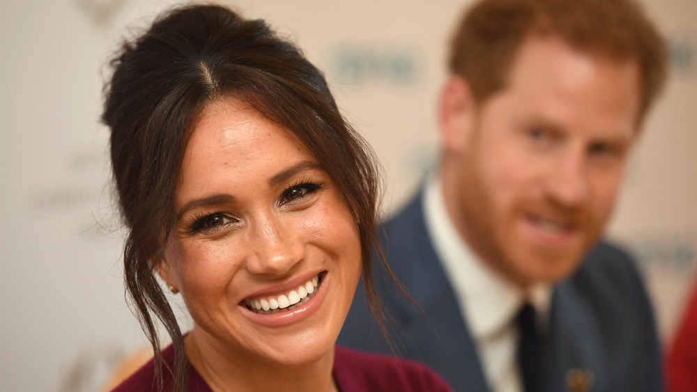 Meghan Markle smiling with Prince Harry in the background