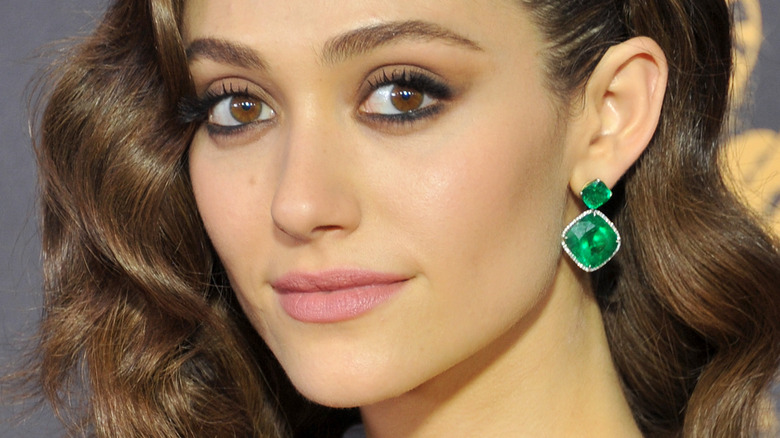 Emmy Rossum smiling and wearing green earrings