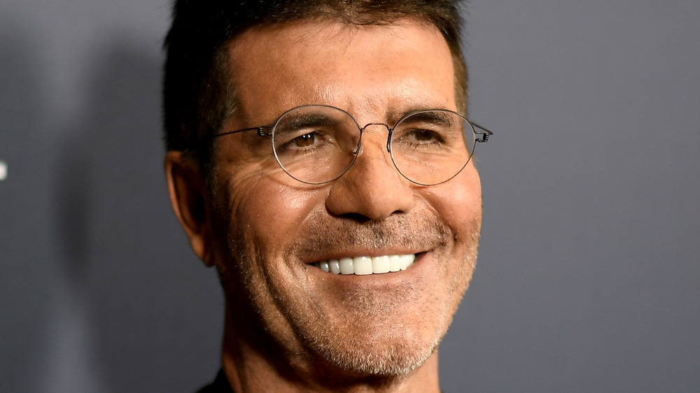 Simon Cowell smiling in glasses