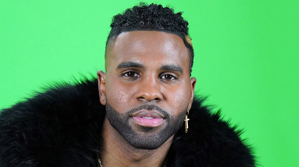 Jason Derulo in a black fur coat and a gold cross earring, in front of a green screen
