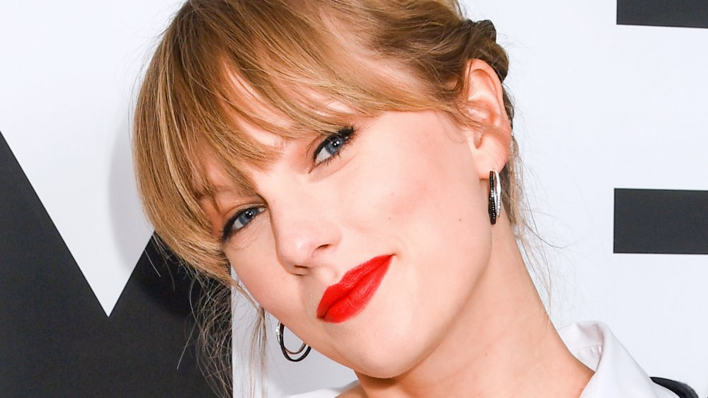 Taylor Swift smirking while tilting her head