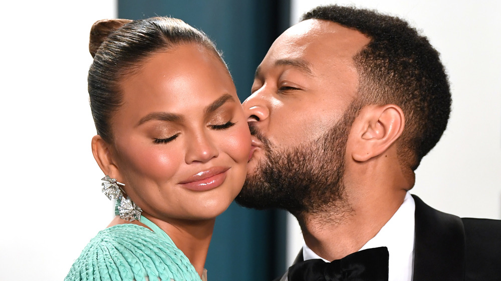 John Legend kissing his wife Chrissy Teigen on the cheek