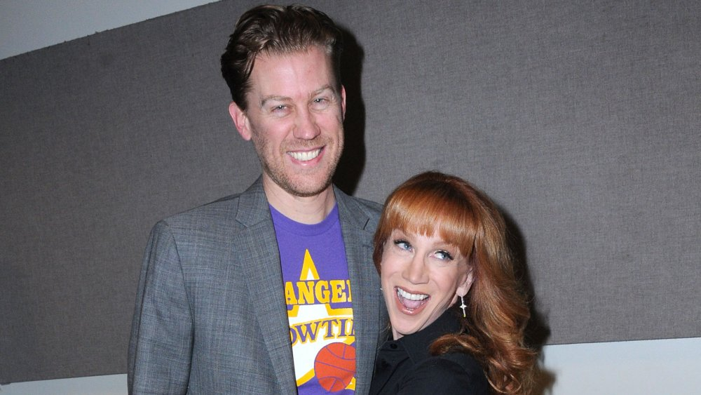 Randy Bick in a grey blazer and purple t-shirt, Kathy Griffin in a black outfit, both smiling