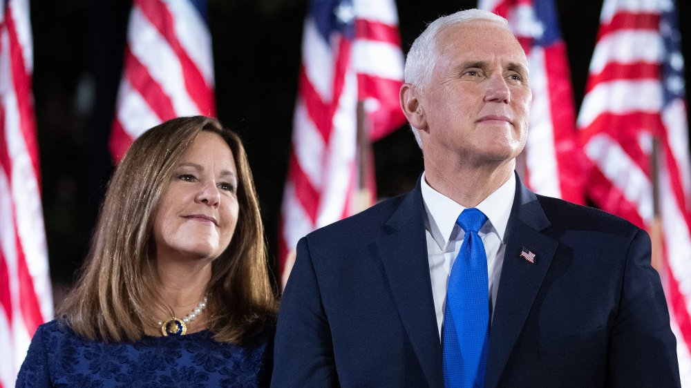 Karen and Mike Pence both gazing and smiling in front of USA flags