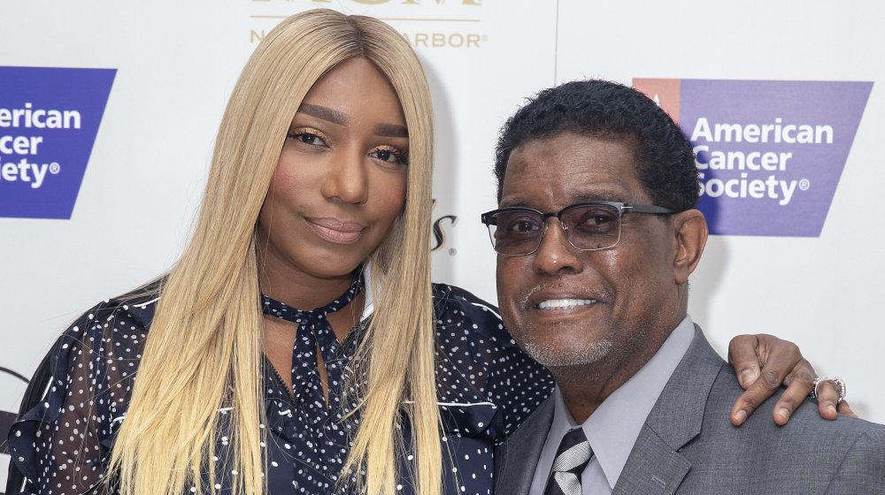 NeNe Leakes in a black-and-white polka-dotted top, Gregg Leakes in a gray suit, both smiling at an American Cancer Society event