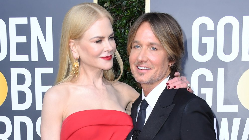 Nicole Kidman in a red dress with her arm around Keith Urban's shoulder