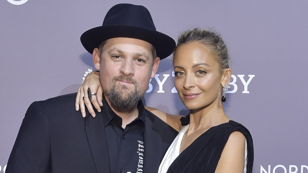 Joel Madden in a black suit and hat, Nicole Richie in a white-and-black dress, posing with their arms around each other and small smiles