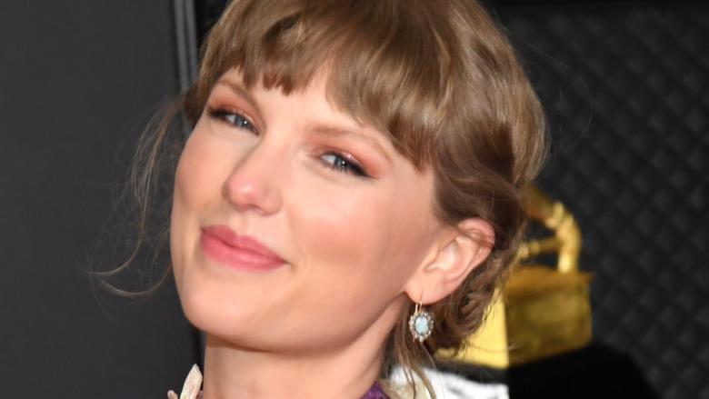 Taylor Swift smirking and holding Grammy Award