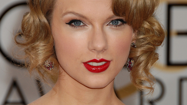 Taylor Swift smiling and wearing red lipstick