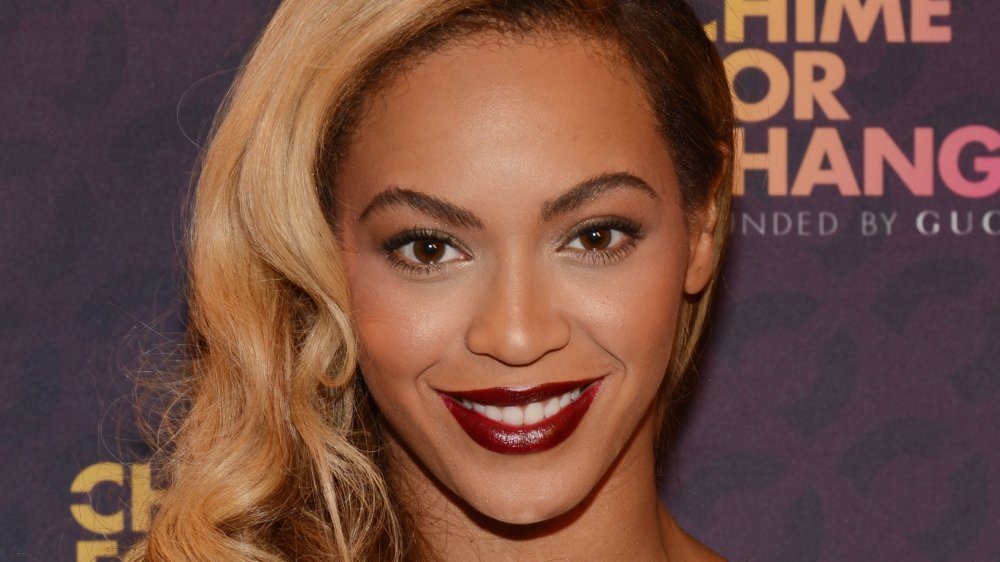 Beyoncé with long blonde hair and dark red lipstick, smiling