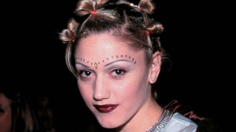 Gwen Stefani wearing a bindi and beads above her eyes with a knotted braid hairstyle