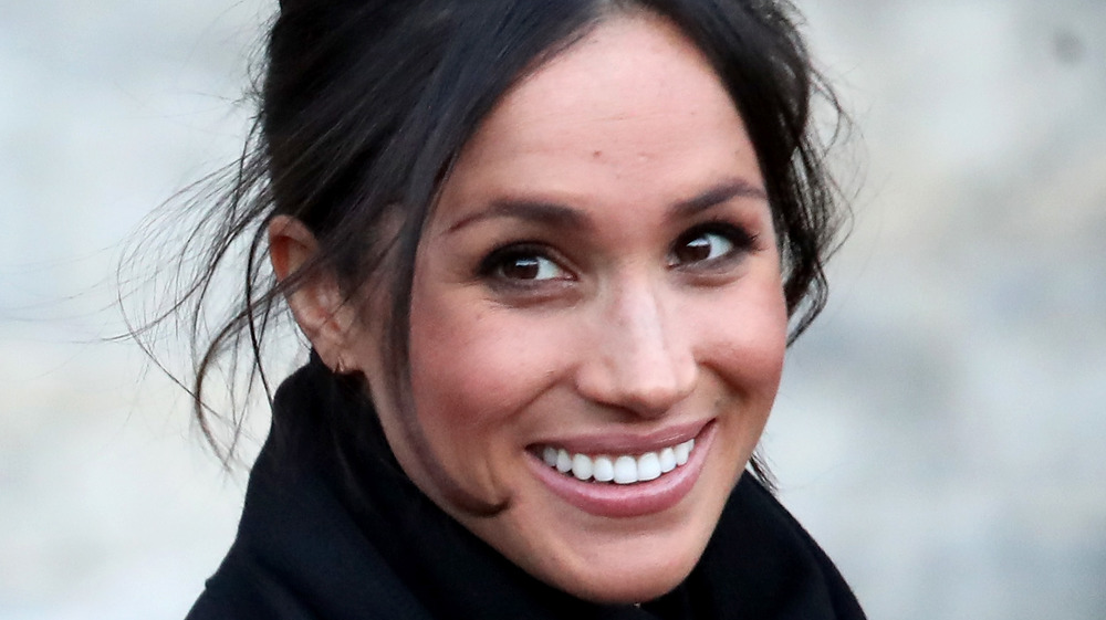 Meghan Markle smiling with her hair in an updo