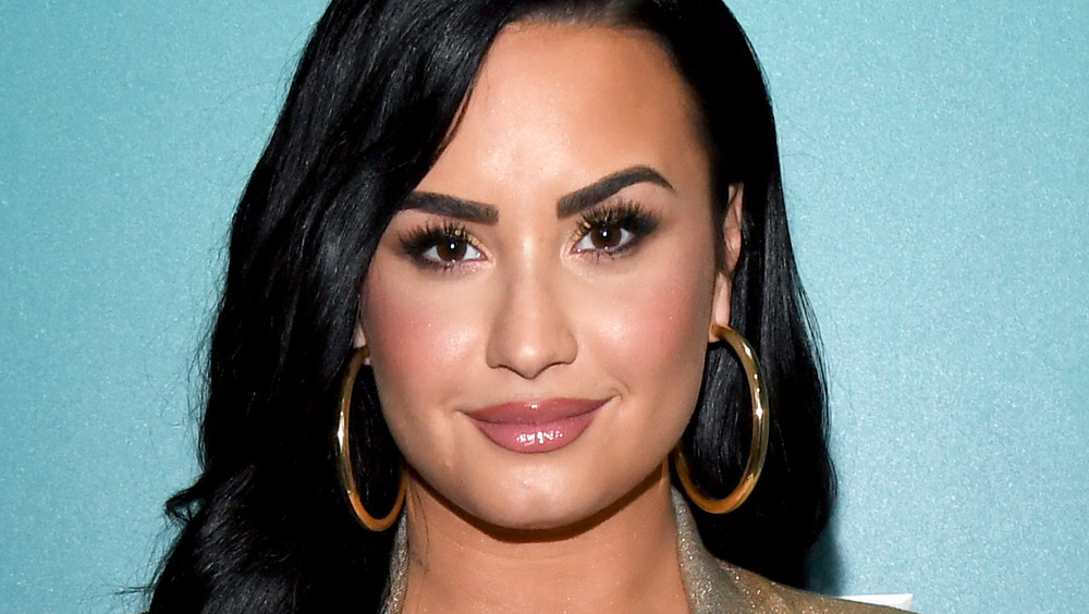 Demi Lovato poses with large hoop earrings.