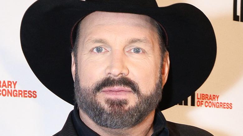 Garth Brooks poses in a black cowboy hat