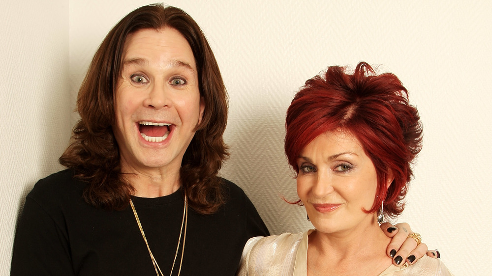 Ozzy Osbourne smiling big and Sharon Osbourne smirking