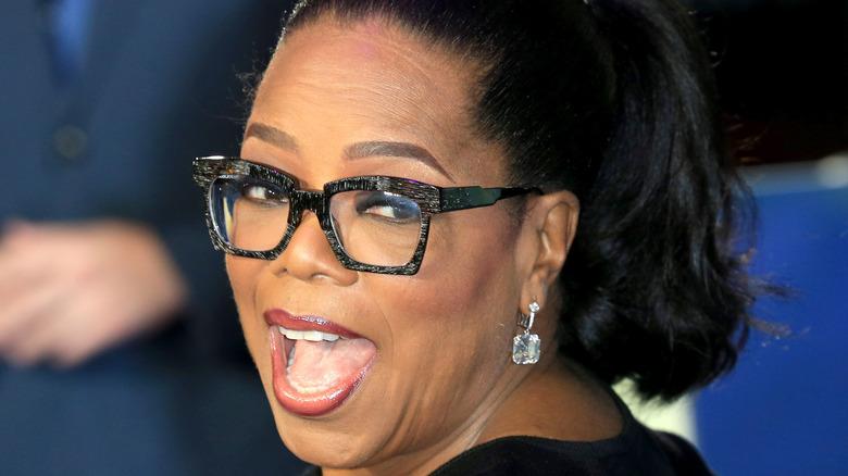Oprah Winfrey smiling big over shoulder