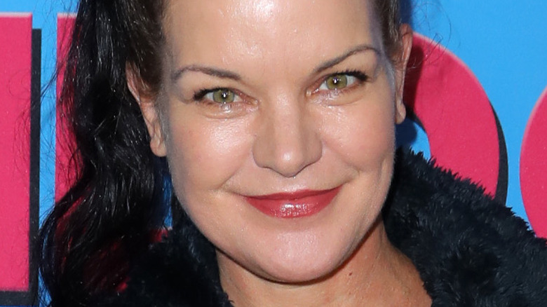 Pauley Perrette wearing ponytail and smiling