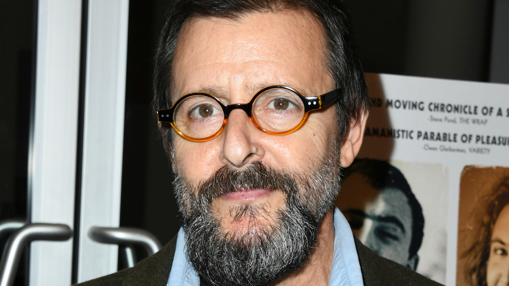 A bearded Judd Nelson smirking and wearing glasses
