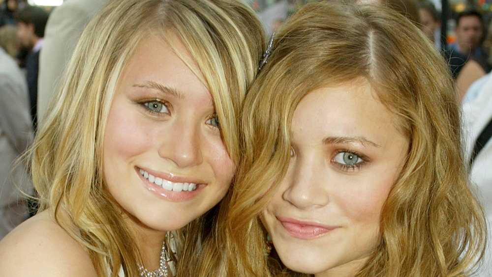 Mary-Kate and Ashley Olsen smiling at an event