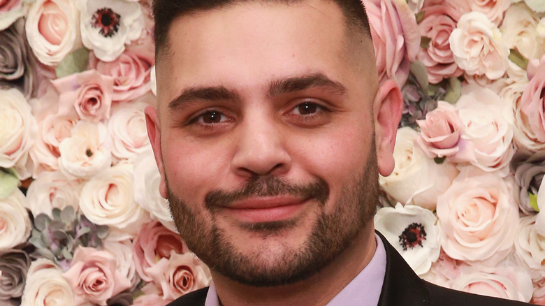 Michael Costello in front of a wall of flowers