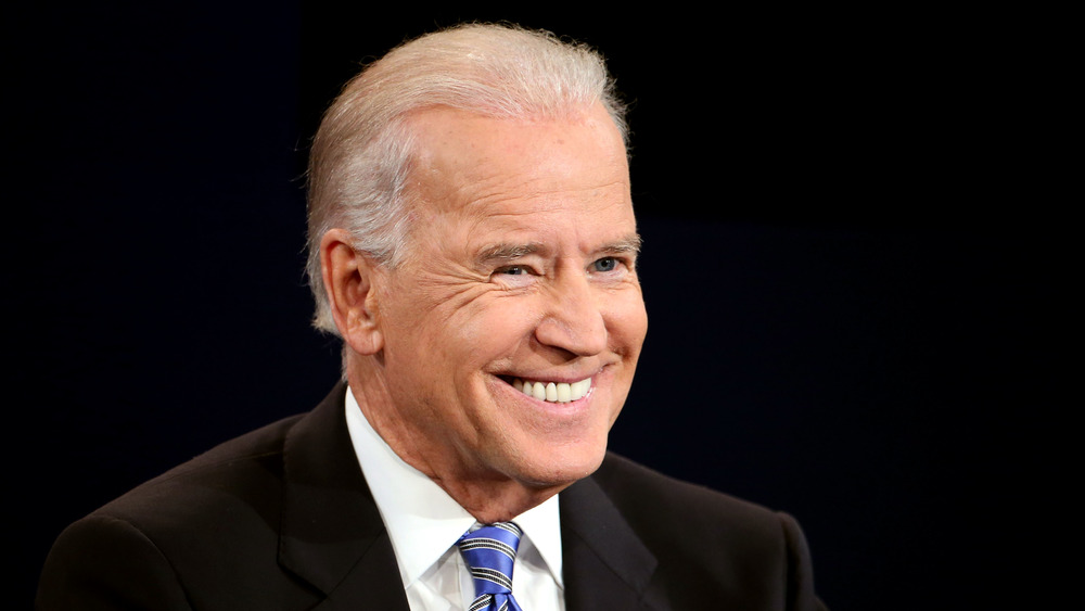 Joe Biden smiles on stage while wearing a suit and blue tie