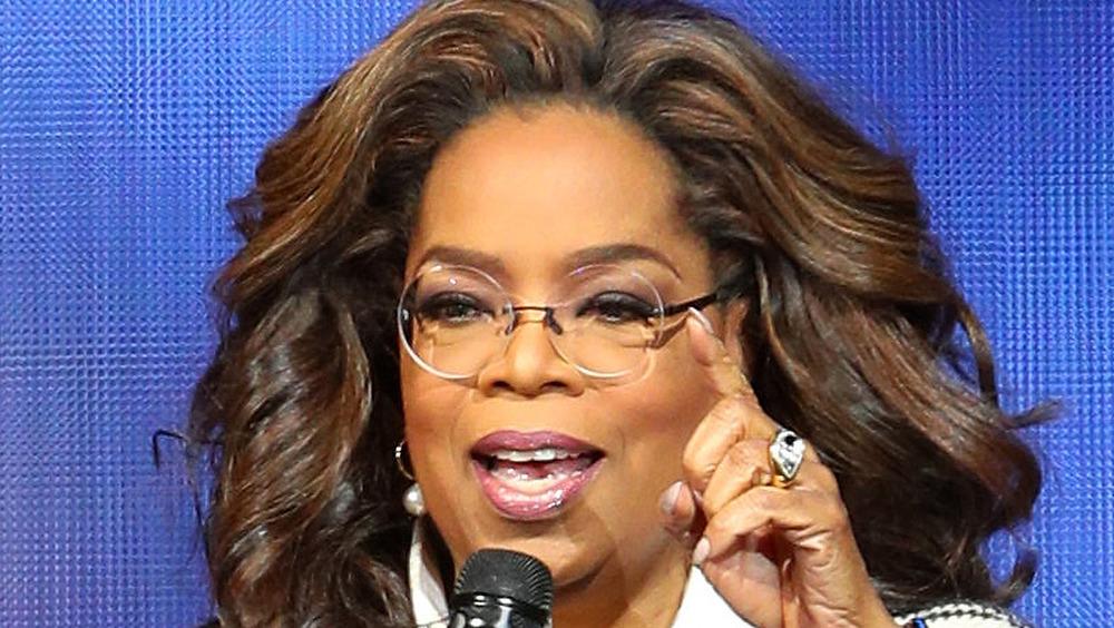 Oprah Winfrey talking into a microphone wearing glasses
