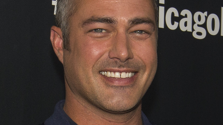 Taylor Kinney smiling on step and repeat
