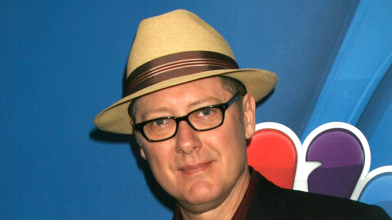 James Spader smiling in glasses and a hat