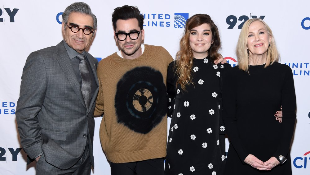 Eugene Levy, Dan Levy, Annnie Murphy, Catherine O'Hara smiling and embracing on a red carpet