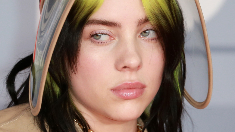 Billie Eilish with green hair and visor looking to side