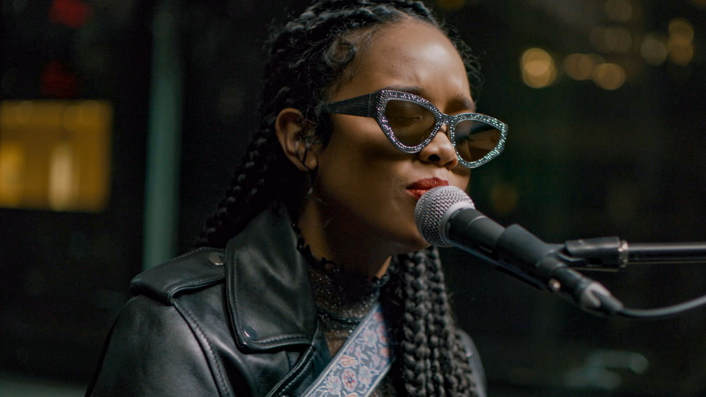 H.E.R performing while wearing sunglasses