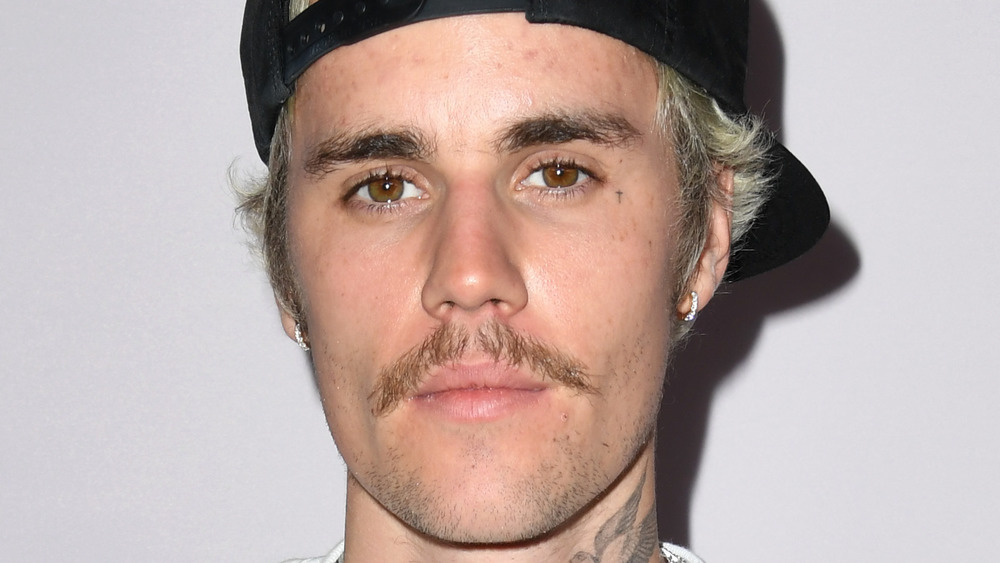 Justin Bieber sporting a mustache, backwards hat, and a serious look