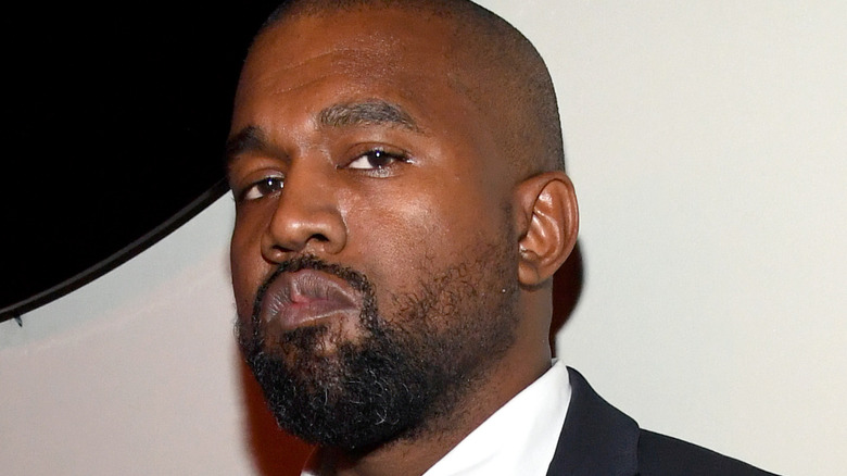 Kanye West wearing a suit with serious expression