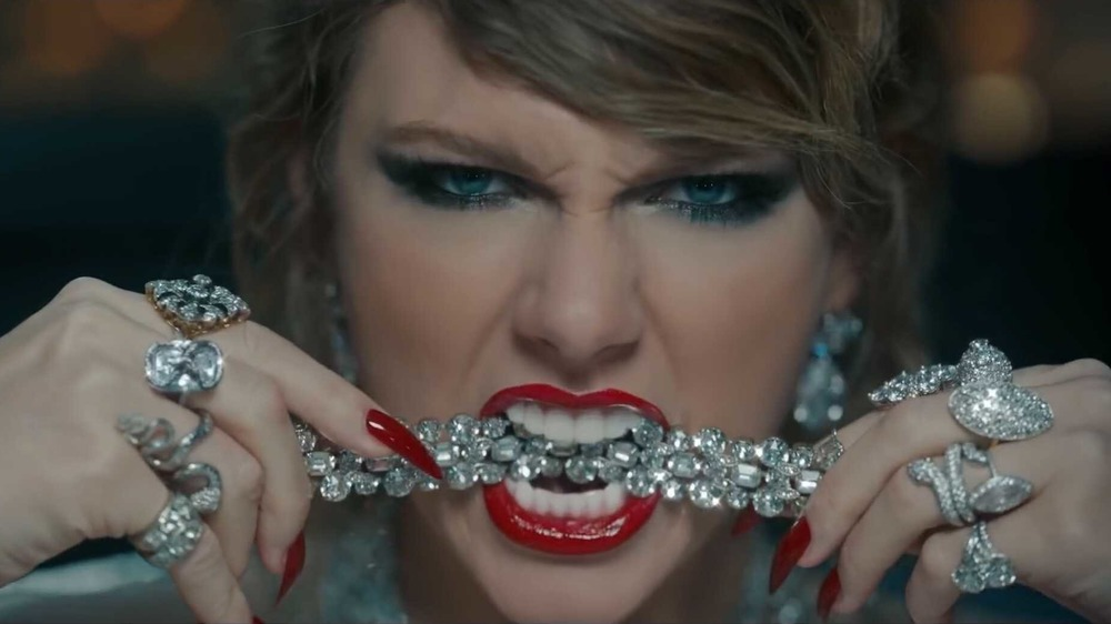 Taylor Swift biting down on a piece of diamond jewelry