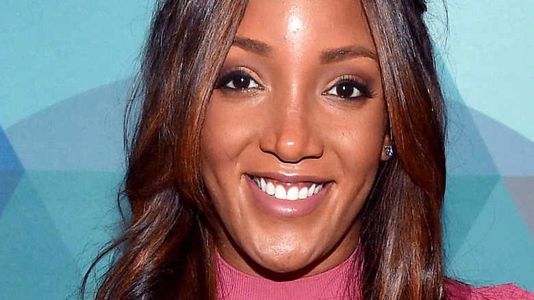 Mickey Guyton smiles on the red carpet