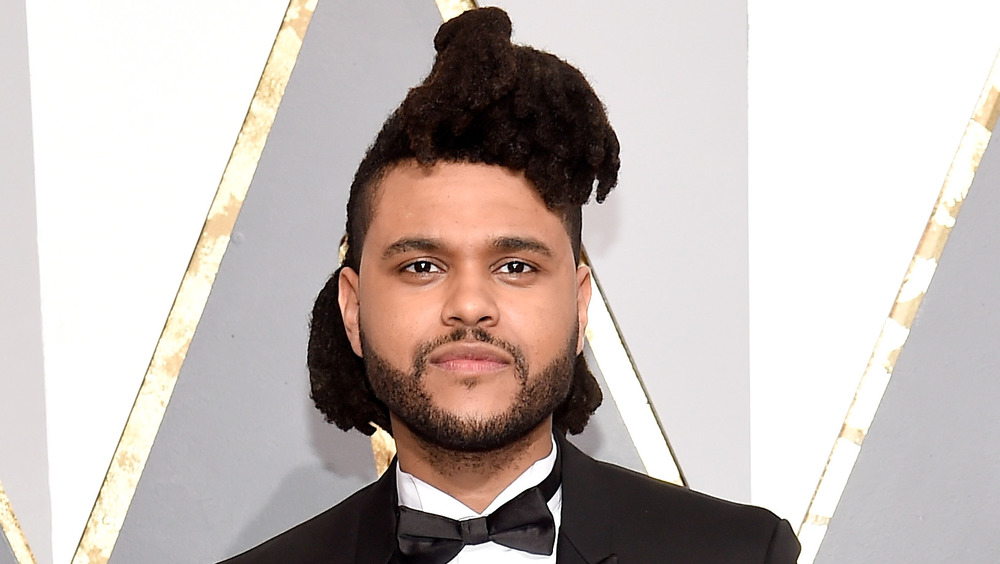 The Weeknd smirking on the red carpet