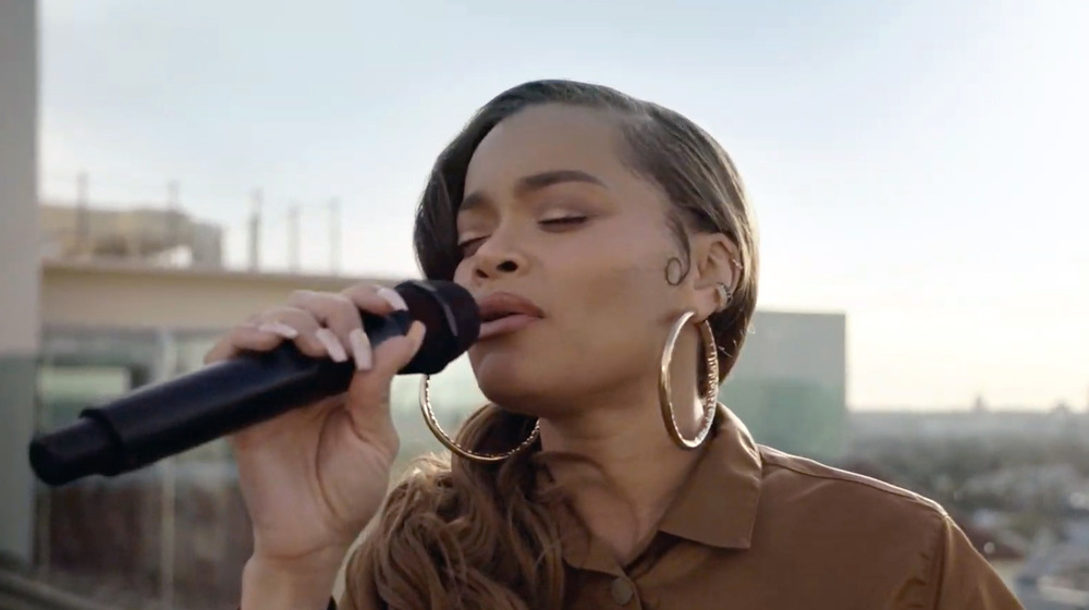 Andra Day singing in a microphone
