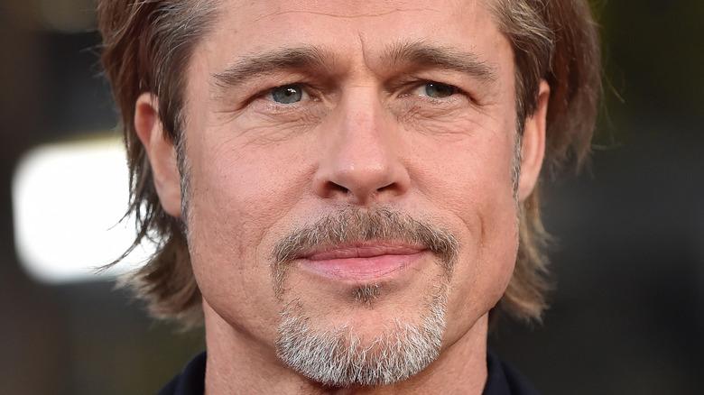 Brad Pitt sporting a scruffy, graying beard smiling