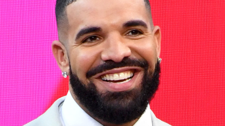 Drake in a grey suit against a pink background