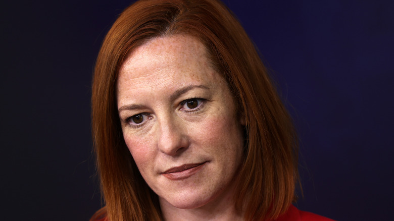 Jen Psaki, not smiling, looking at someone, wearing makeup, in a press briefing from March 2021