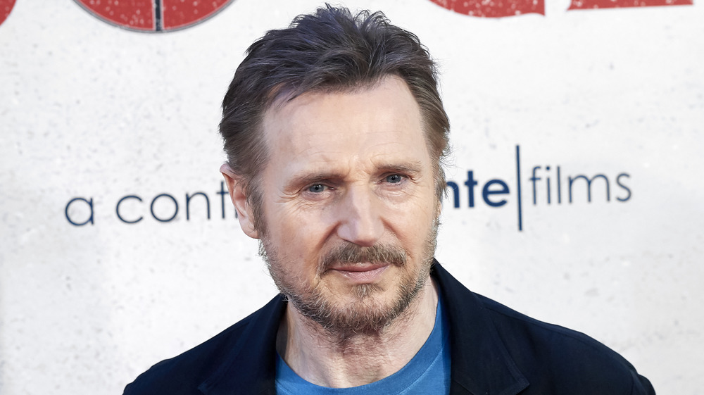 Liam Neeson with a beard posing on the red carpet