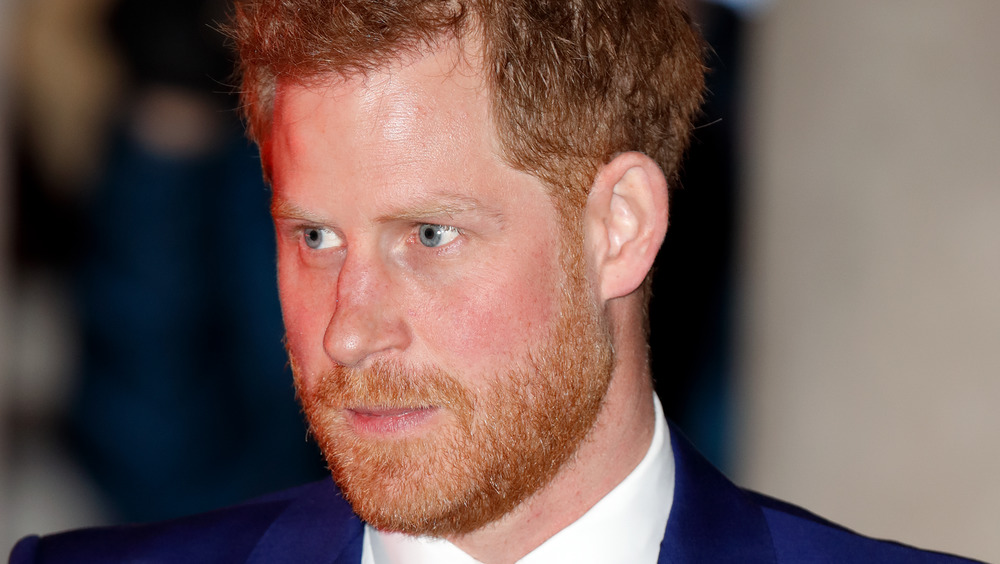 Prince Harry staring into the distance wearing a blue suit
