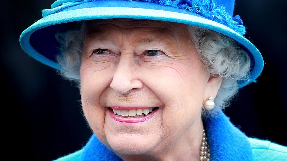 Queen Elizabeth II wears a blue hat