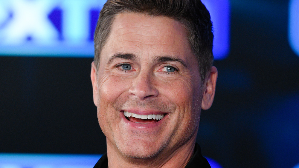 Rob Lowe smiles at the camera during an interview