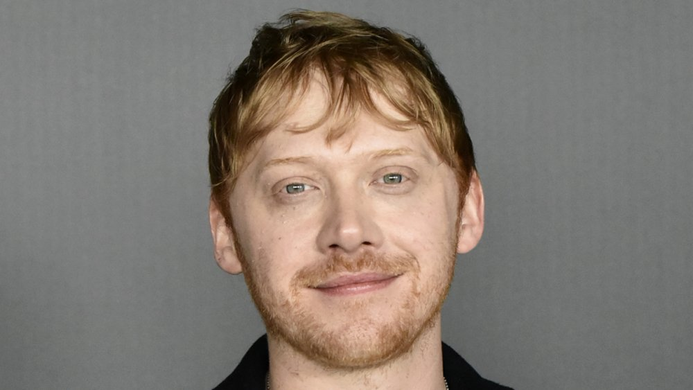 Rupert Grint wearing a black blazer, with a small smile, at an event